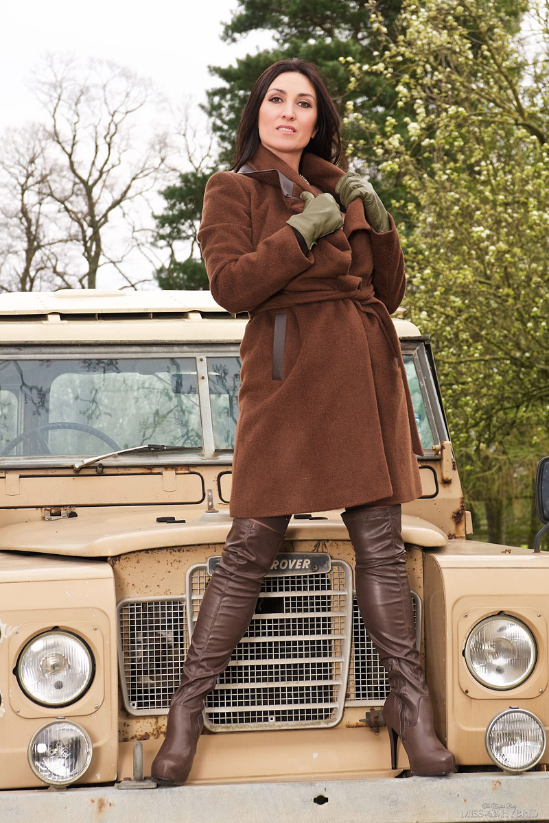 Miss Hybrid May newsletter leather thigh boots on the Land Rover Bonnet.
