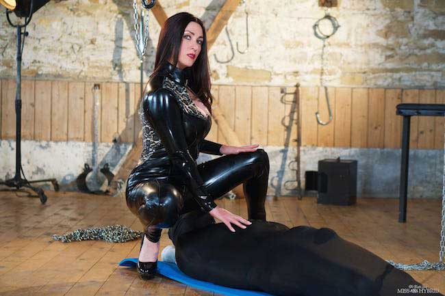 Cock humiliation Miss Hybrid teases her slave in skin tight latex.
