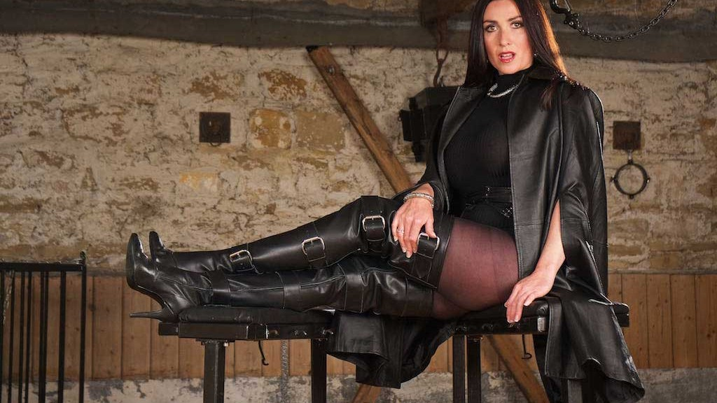 Miss Hybrid leather booted mistress playing in the dungeon.