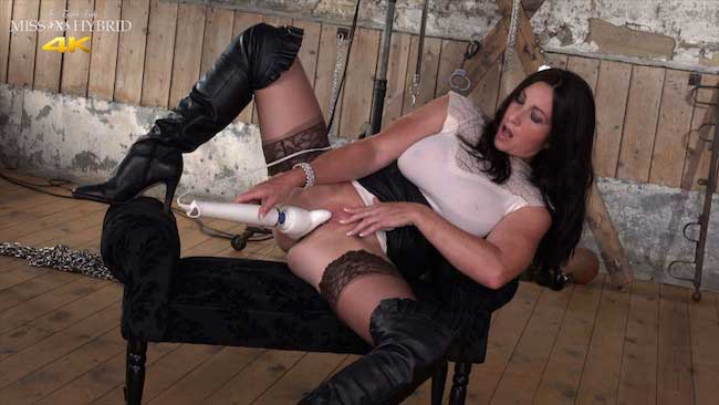 Miss Hybrid Leather booted mistress in the dungeon with butt plug and magic wand.