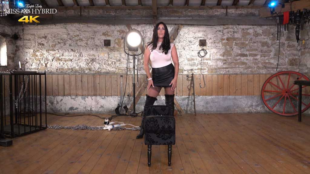 Leather booted mistress Miss Hybrid leather skirt and thigh boots in the dungeon.
